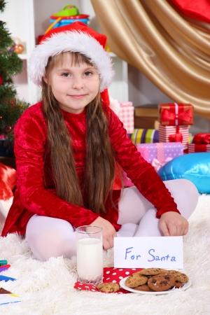 festively: Beautiful little girl with milk and cookies for Santa Claus in festively decorated room Stock Photo