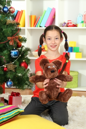 Little girl holding toy near christmas tree Stock Photo - 17129920