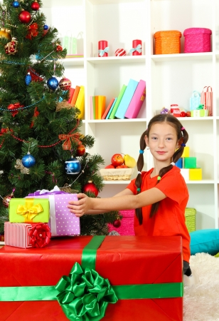 Little girl with large gift box near christmas tree Stock Photo - 17129922