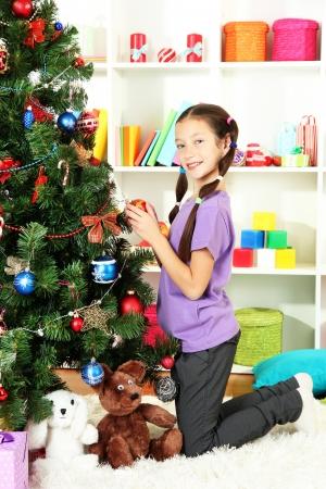 Little girl decorating christmas tree photo