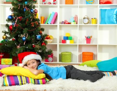 Little girl sleeping near christmas tree photo