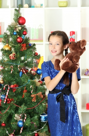 Little girl holding toy near christmas tree Stock Photo - 17129776