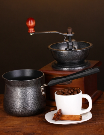 Coffee maker with coffe mill and white cup on wooden table photo