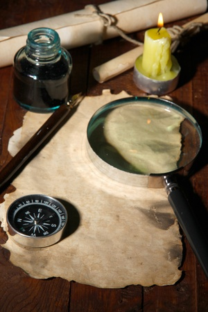 Old paper with ink pen and magnifying glass near lighting candle on wooden table photo