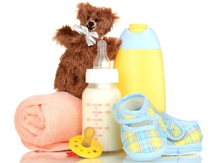 comida rica: Botella de leche, chupetes y cosmética bebé con la toalla aislada en blanco Foto de archivo