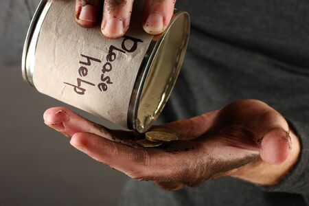 waster: homeless pours money from bank, close-up Stock Photo