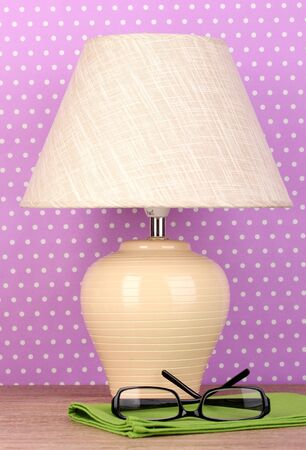 table lamp and glasses on purple polka dot background photo