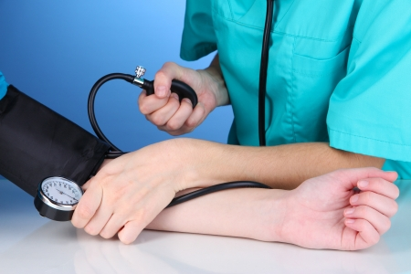 Blood pressure measuring on blue background photo