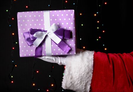 Santa Claus hand holding gift box on bright background Stock Photo - 16738451