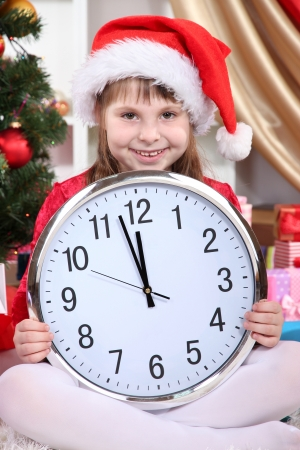 festively: Beautiful little girl with clock in anticipation of New Year in festively decorated room Stock Photo