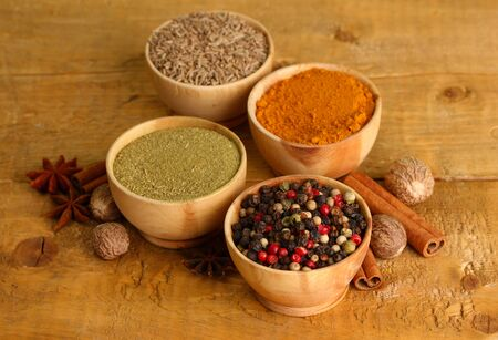 bowls with spices, on wooden background photo