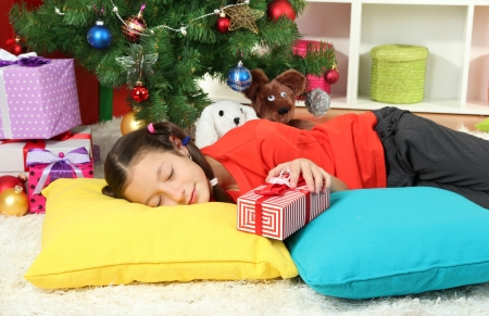 Little girl sleeping near christmas tree Stock Photo - 17129961