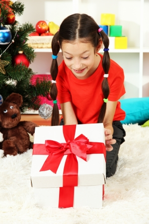 Little girl with present box near christmas tree photo