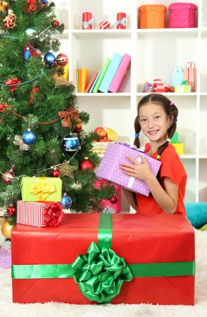 Little girl with large gift box near christmas tree Stock Photo - 17129963