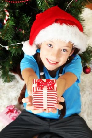 Little girl holding gift box near christmas tree Stock Photo - 17129954