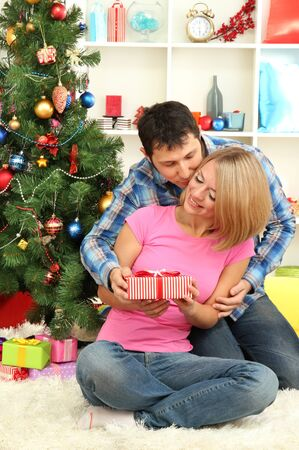 Young happy couple with presents sitting  near Christmas tree at home Stock Photo - 17132708