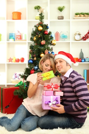 Young happy couple with presents sitting  near Christmas tree at home Stock Photo - 17178427