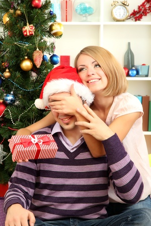Young happy couple with presents sitting  near Christmas tree at home Stock Photo - 17187368