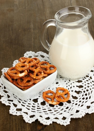 Tasty pretzels in white bowl and milk jug on wooden table close-up Stock Photo - 16738641