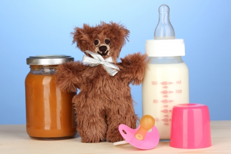 Baby food, bottle of milk, puree with teddy bear on blue background photo