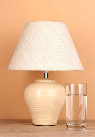table lamp and glass of water on beige background Stock Photo - 16738611
