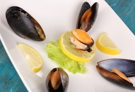 Snack of mussels and lemon on plate on blue wooden table photo