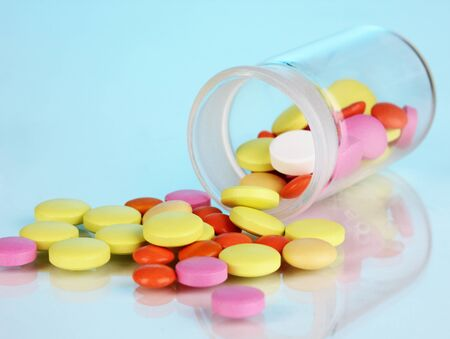 Pills in receptacle on blue background Stock Photo - 16788092