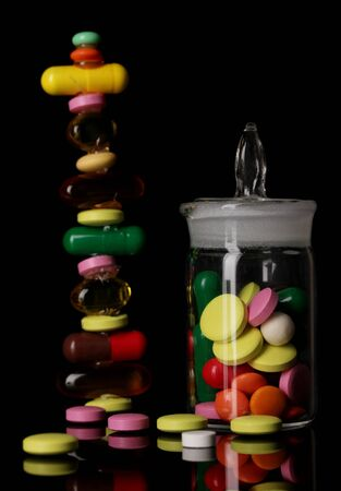receptacle: Capsules and pills hill and in receptacle isolated on black