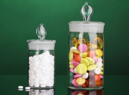 Capsules and pills in receptacles on green background photo