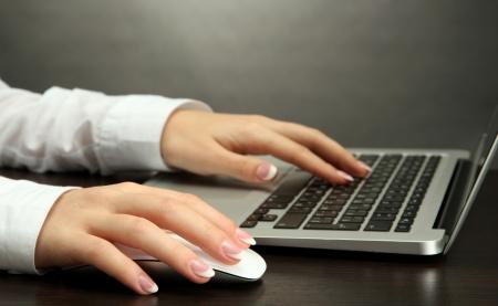 female hands writing on laptot, on grey background Stock Photo - 16788074
