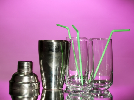 Cocktail shaker and glasses on color background photo