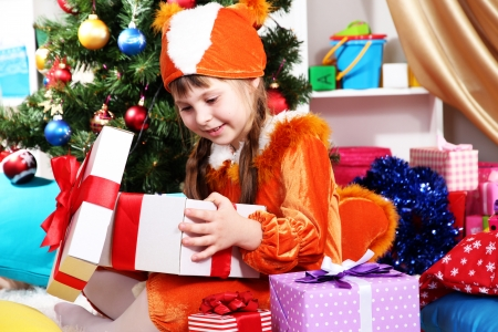 festively: Little girl in suit of squirrels opens gift in festively decorated room Stock Photo