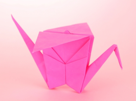 Origami crane on pink background  photo