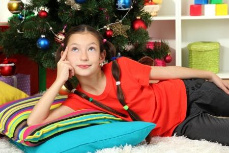 Little girl dreaming near christmas tree photo