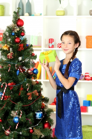 Little girl holding gift box near christmas tree Stock Photo - 17129975