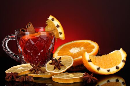 Fragrant mulled wine in glass with spices and oranges around on red background photo