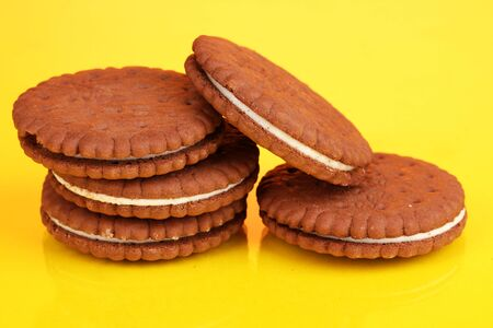 nutritiously: Chocolate cookies with creamy layer on yellow background
