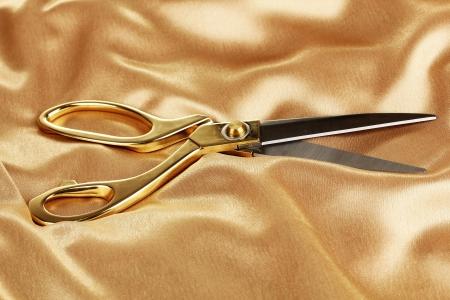 Metal scissors on gold fabric photo