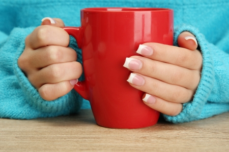 cold weather: hands holding mug of hot drink, close-up