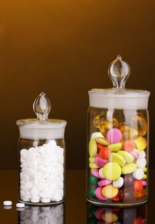 Capsules and pills in receptacles on orange background Stock Photo - 16805356