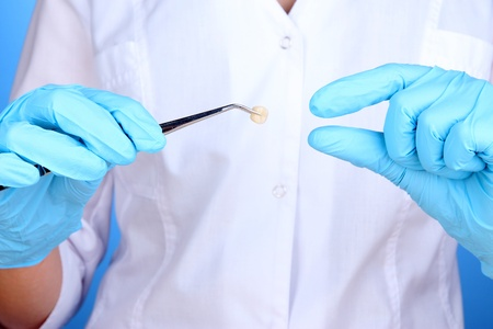 A dentists hands in blue medical gloves with dental tools Stock Photo - 16805316