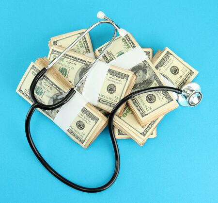 Healthcare cost concept: stethoscope and dollars on blue background photo