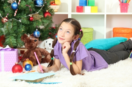 Little girl writing letter to Santa near christmas tree Stock Photo - 17129550