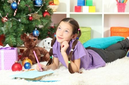 Little girl writing letter to Santa near christmas tree Stock Photo - 17129550
