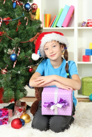 Little girl holding gift box near christmas tree Stock Photo - 17129571