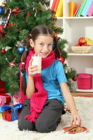 Little girl with pink scarf and glass of milk sitting near christmas tree photo