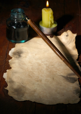 table scraps: Old paper with ink pen near lighting candle on wooden table Stock Photo