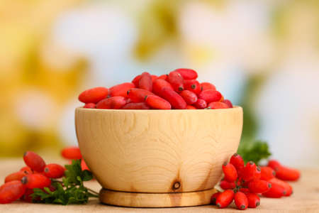ripe barberries in wooden bowl with green leaves, on table photo