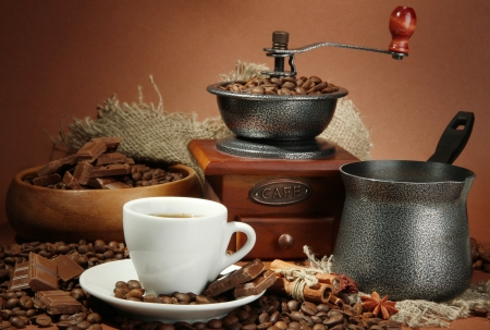 cup of coffee, grinder, turk and coffee beans on brown background Stock Photo - 16805816