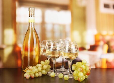 glass of white wine: White wine in glass and bottle on room background